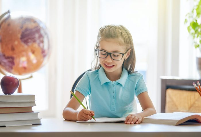 child is sitting at a desk indoors
