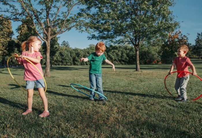 Happy preschool children kids friends playing with hoola hoops in park outdoor on summer day.