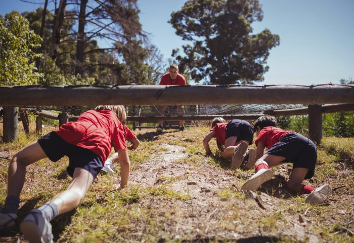 Kids crawling under the net during obstacle course training